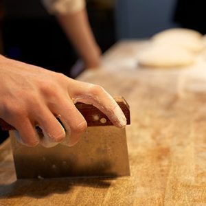 Baker portioning dough with bench scraper at bakery